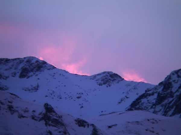 Besneeuwde toppen met daarachter paarse flarden