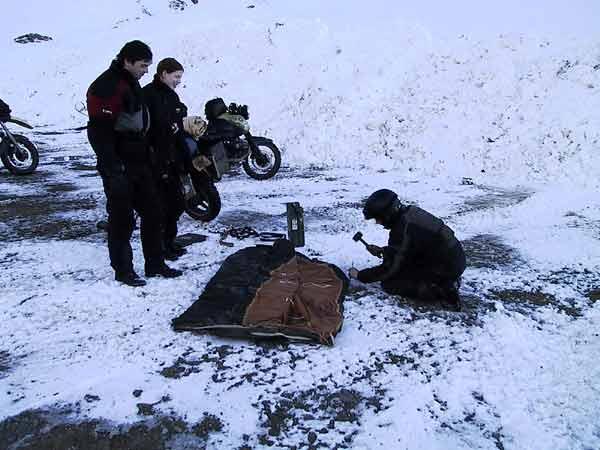 Hans probeert een haring in het asfalt te tikken met een hamer
