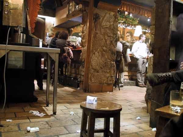 Café met mensen aan de bar en rommel op de grond