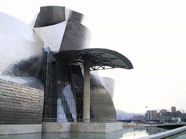 Een gebouw met ronde en puntige vormen in titanium, omgeven door water