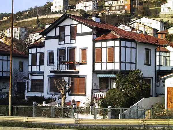 Wit huis, rode pannendaken, zwart vakwerk bij erkers