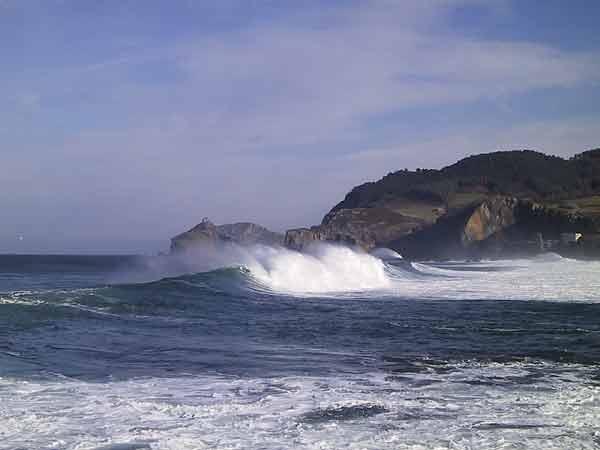 Donkere rotsen steken uit in een bl;auwe zee, schuimkoppen op de golven