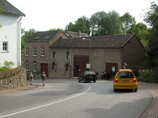 ANWB auto komt aanrijden, in straat met boerderij in bocht naar beneden