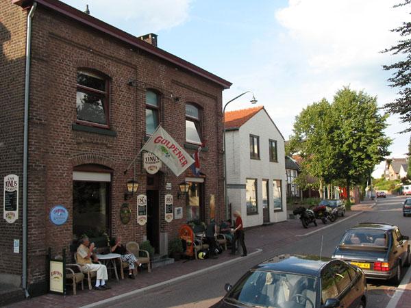 Café met Gulpener vlag en klein terrasje op smalle stoep