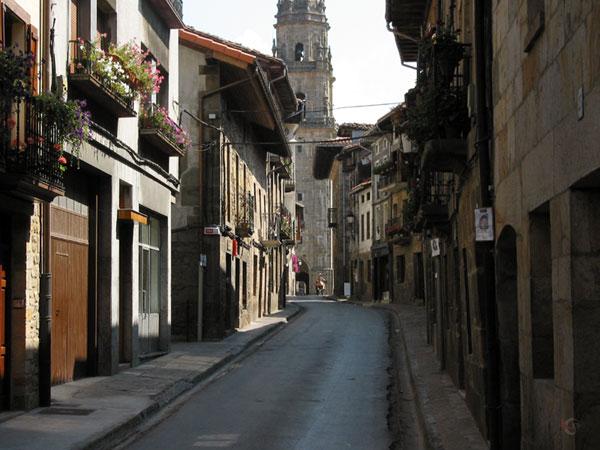 Heel smal straatje met kertoren aan het einde