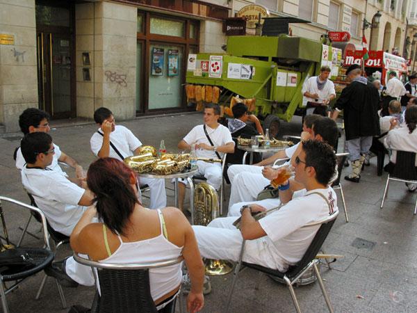 Jonge mensen aan terrastafel, muziekinstrumenten op tafel, allemaal in het wit gekleed