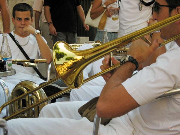 Jongen met trombone aan de mond op terrasje