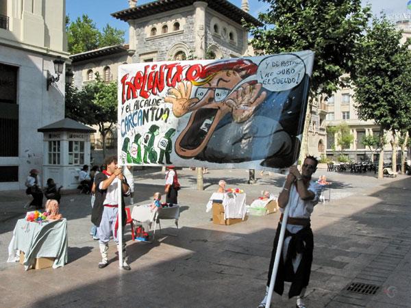 Twee jongens in klederdracht met spandoek met karikatuur en Baskische tekst