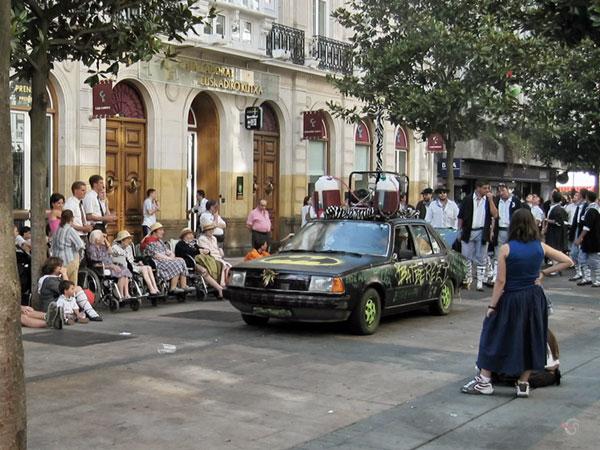 Beschilderde auto, reuzen bierglazen er bovenop, toeschouwers waaronder een rijtje oude vrouwtjes
