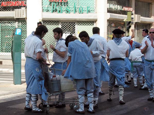 Jongens in klederdracht om supermarktkarretje met drinken
