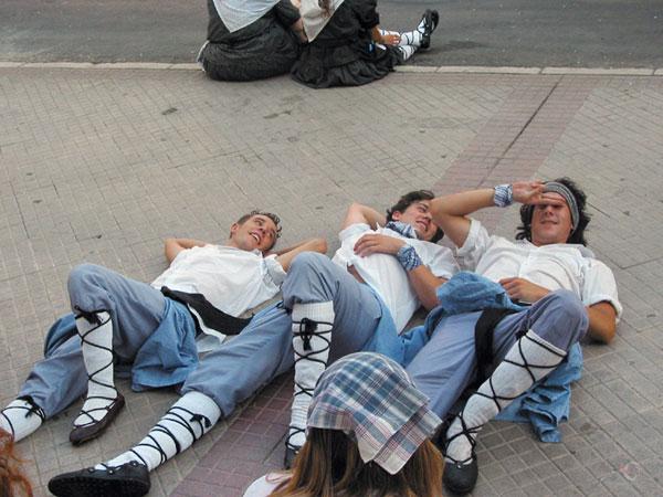Drie jongens in klederdracht liggen op het trottoir