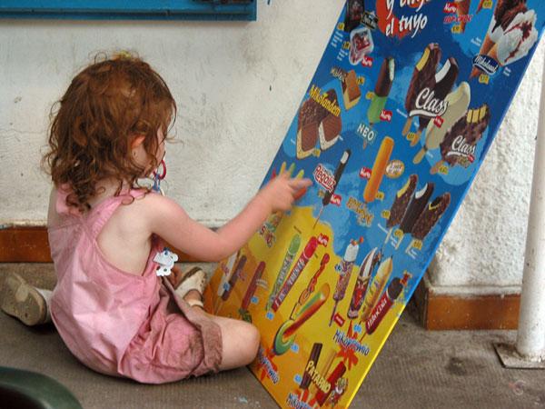 Klein meisje met rode haren op haar knietjes voor een poster met ijs