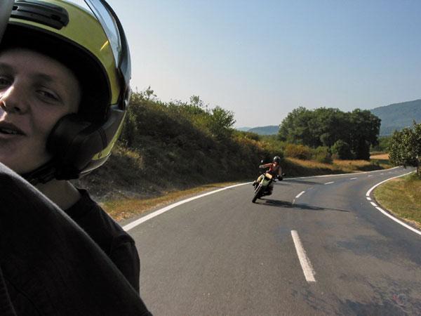 Pieter's hoofd met helm, Sylvia daar achter op de motor