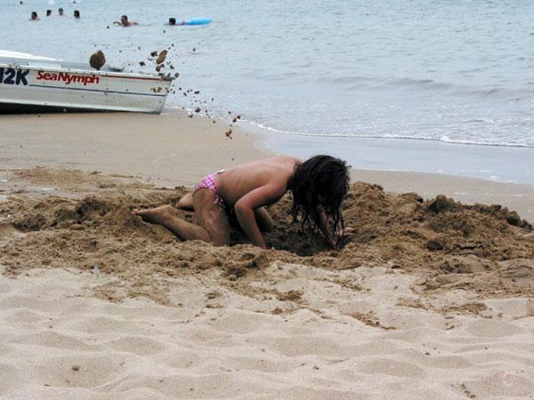 Klein meisje graaft enorme kuil op het strand