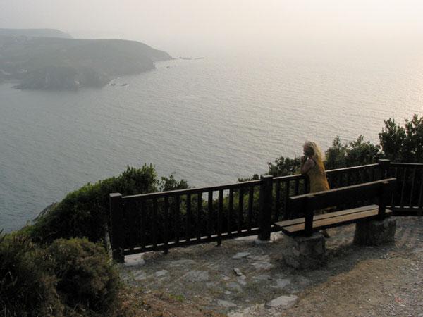 Sylvia bovenop rots met uitzicht over baai
