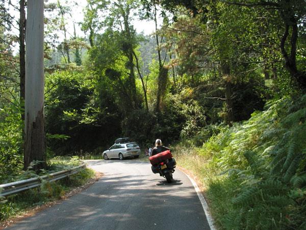 Motor rijdt aan op bocht met auto aan de kant