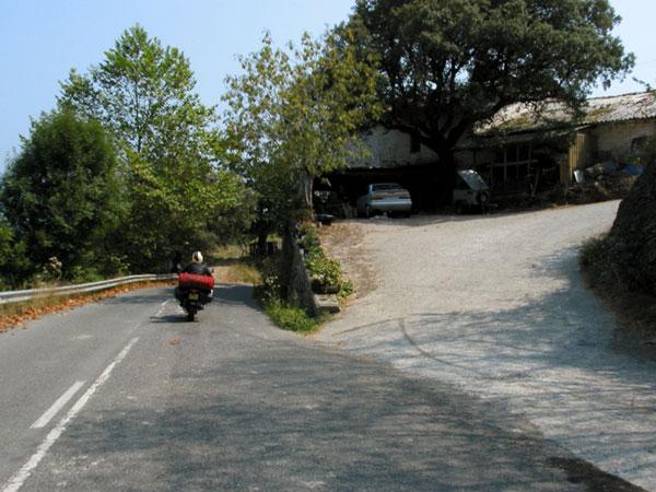 Sylvia op motor langs huis met oprit naar garage