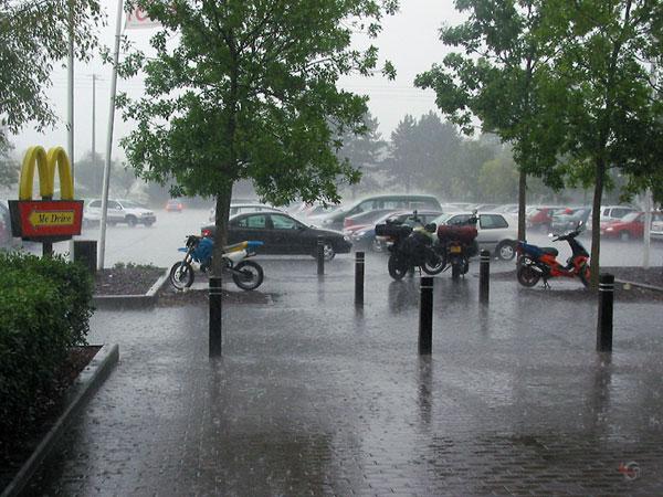 De motoren op een parkeerplaats in een stortregen