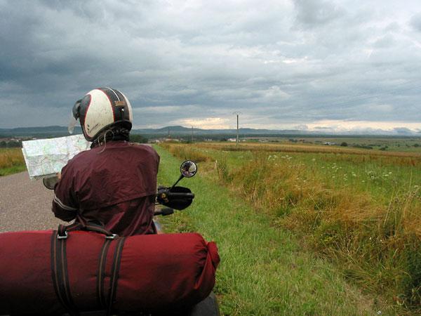 Sylvia stilstaand met motor met kaart, donkere wolken in de verte