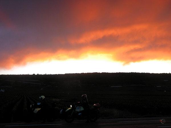 Twee motoren in het donker met daarboven een oranje lucht