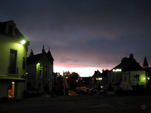 Huizen rond een pleintje, verlicht door straatlantarens