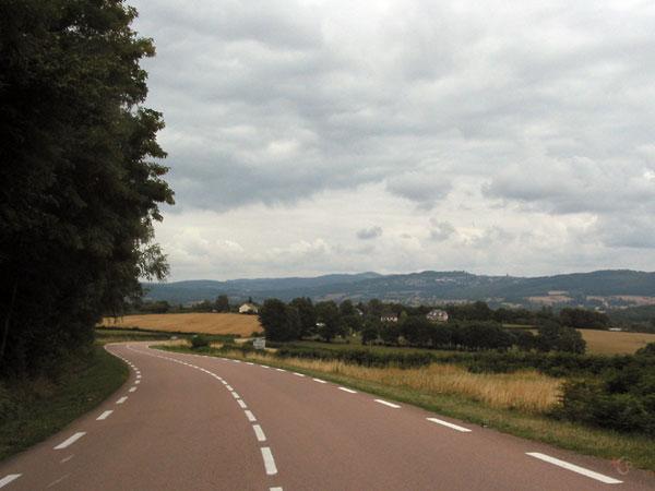 Bochtige weg, heuvels in de verte, bos