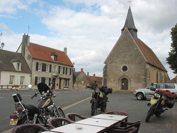 Onze motoren met een motorvriendje bij een terras, kerk op de achtergrond