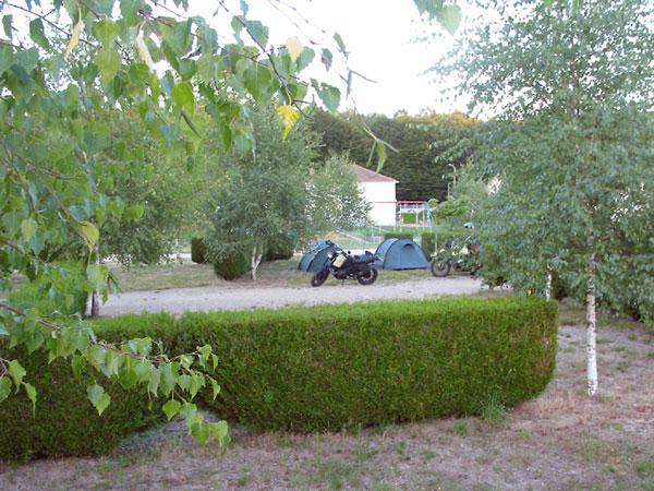 De motoren en twee groene tentjes op een plekje tussen ligusterhagen; camping verder leeg