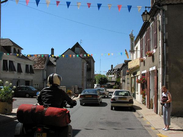 Sylvia op de motor in Frans stadje met slingers over de weg