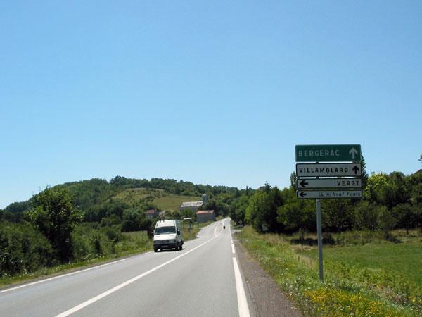 Weg van goed asfalt door groen heuvelig landschap