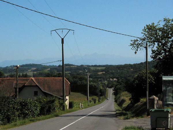 Rechte weg in heuvellandschap, in verte heel vaag de Pyreneeën