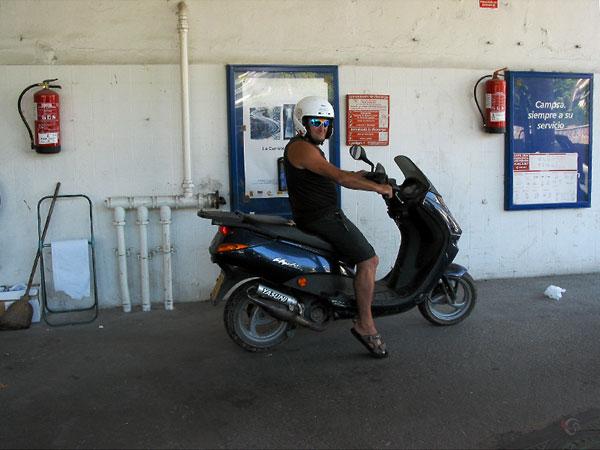 Man in korte broek, met zonnebril, op scootertje