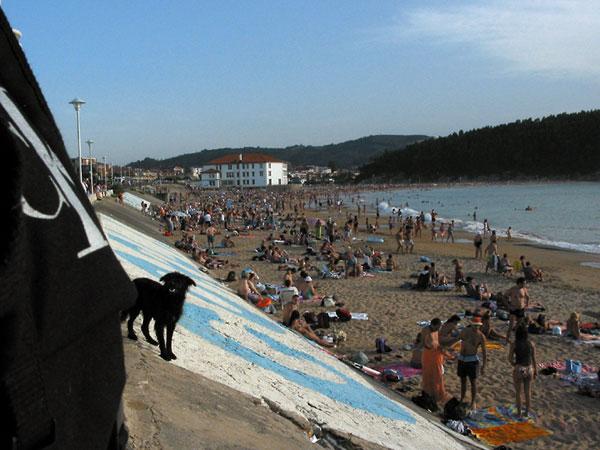 Strand vol mensen, wit huis aan einde baai