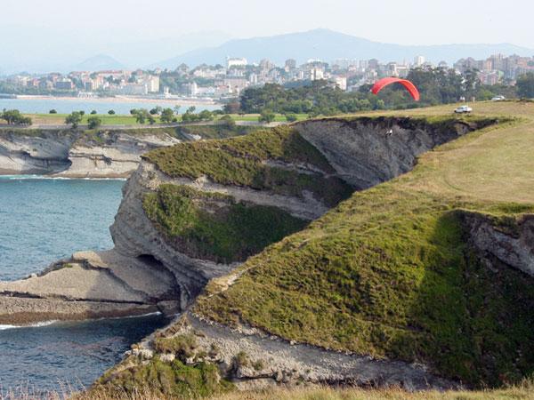 Kliffen, bovenop met gras begroeid, Santander in de verte
