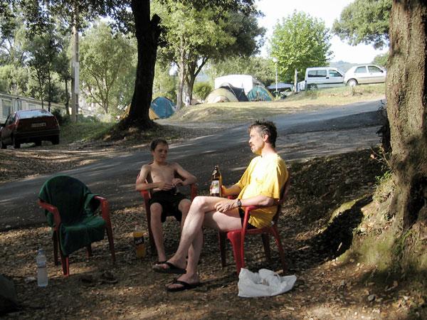 Ernst en Pieter op plastic stoeltjes in de schaduw, flesje bier erbij