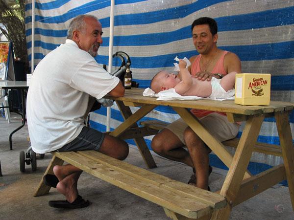 Baby op picknicktrafel, twee mannen erbij