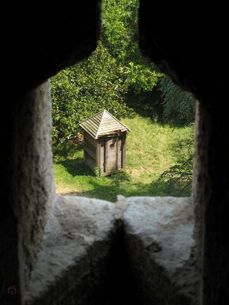 Te zien door opening in muur: houten wc huisje