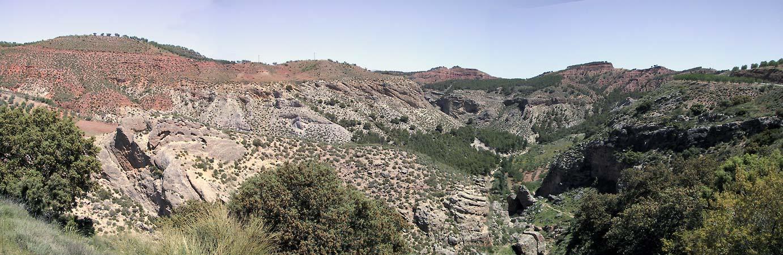 Ravijn met kanten van rode en witte rotsen, begroeid met struiken