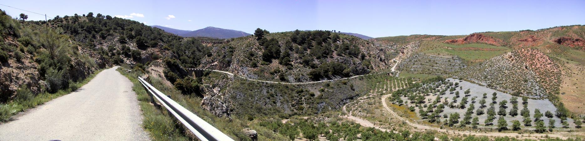 Olijfboomgaarden, heuvels met woestenij, rode aarde, en een weg daar slingerend doorheen