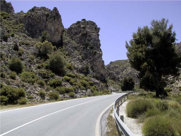 Asfaltweg, met hogere grijze rotsen