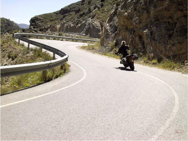 De weg loopt bocht na bocht na bocht langs de rotsige bergwand