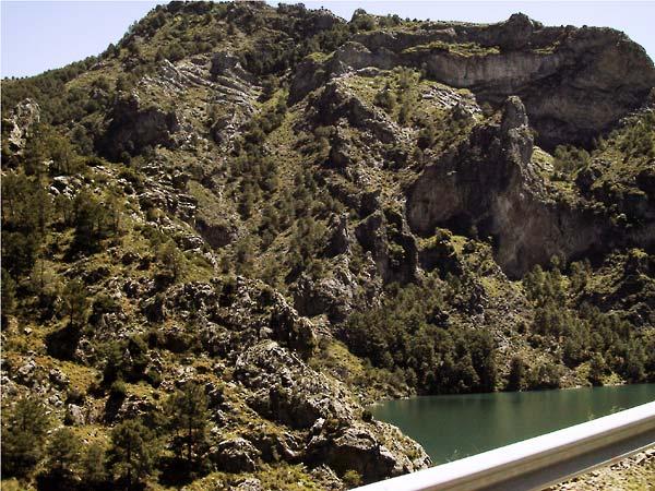 Stuwmeer omsloten door hoge steile donkere rotsen