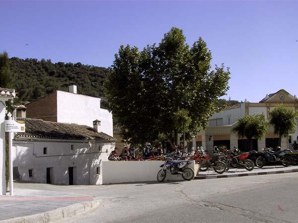 Verzameling crossmotoren op pleintje bij witte huizen