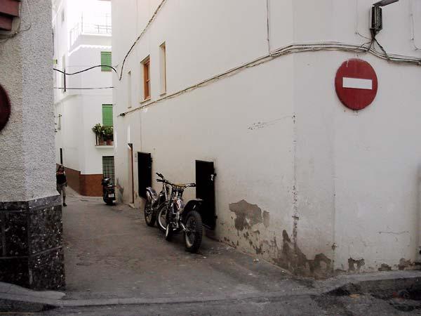 Steegje tussen witte huizen met twee trial-motoren
