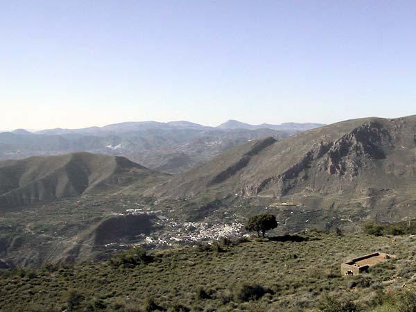 Uitzicht over kale donkere bergen, wit stadje in de diepte