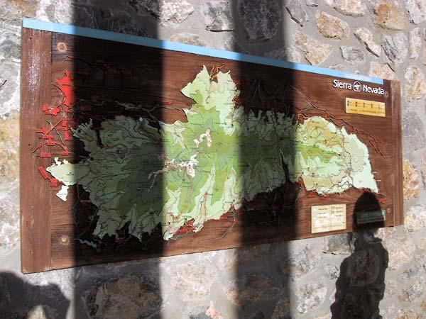Houten bord met kaart van de Sierra Nevada, op ruwstenen muur