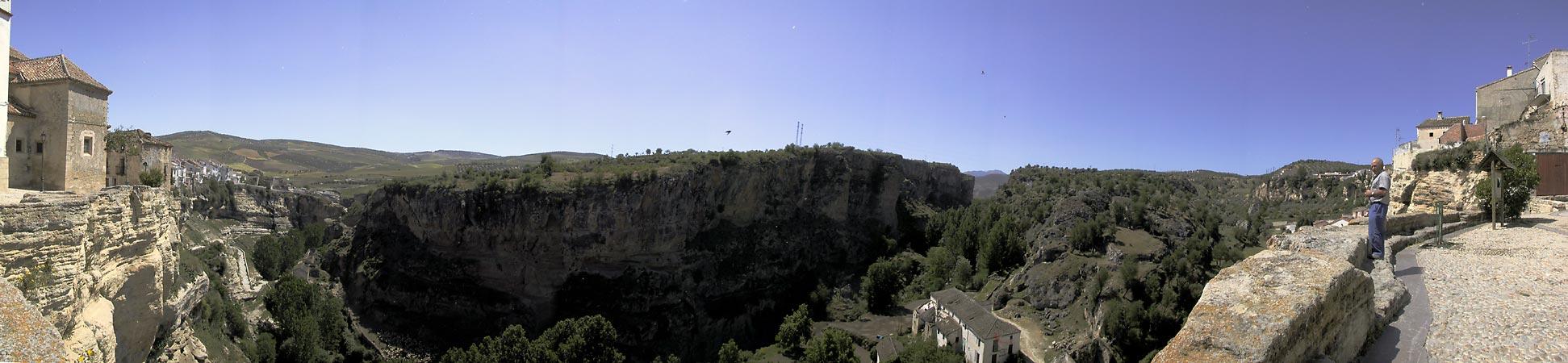 Witte loodrechte rots aan de kant van het stadje; loodrechte grijze rots aan de overkant, bomen in de kloof