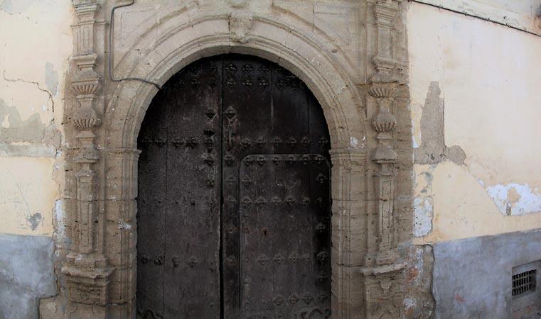 Eeuwenoude houten voordeur met natuurstenen omlijsting in boog