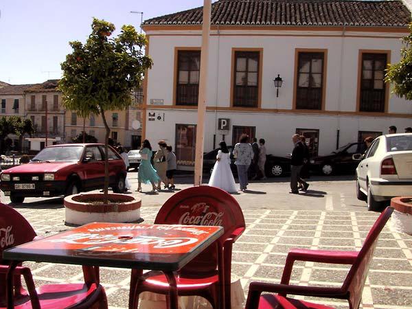 Plein met terras en auto's, en mensen in zondagse kleren, en een meisje in witte jurk