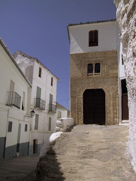 Smal wit huis op verhoging, natuurstenen onderkant met versierde Moorse boog als opening